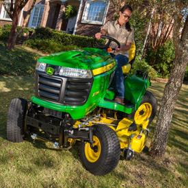 Tractor X734 podando el césped alrededor de un árbol