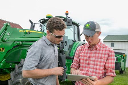 Tracteur6155M de JohnDeere avec récepteur StarFire™6000 et tablette équipée du systèmeJDLink
