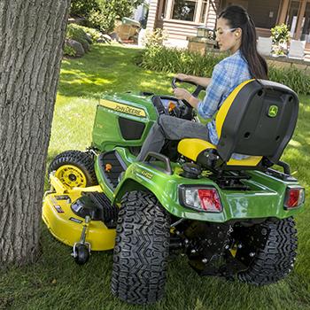 TracteurX739 effectuant des finitions autour d'un arbre