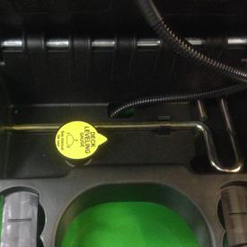 Messlehre für die Horizontalposition des Mähwerks und Sechskant-Einstellwerkzeug unter dem Sitz des Traktors verstaut