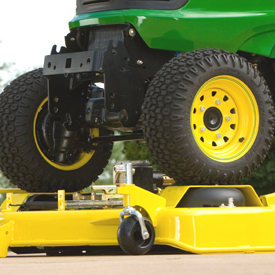 Tracteur à quatre roues motrices (4RM) avançant sur un carter de coupe de grande capacité