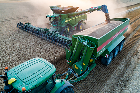 X Series Combine with Hinged Draper header unloading on the go